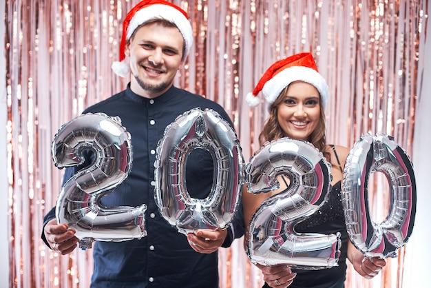 Joven y mujer con sombreros rojos de santa divirtiéndose con 2020 globos metálicos.