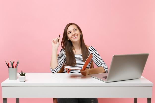 Joven mujer soñadora mirando hacia arriba pensando buscando una nueva idea sosteniendo un lápiz y un cuaderno sentarse a trabajar en un escritorio blanco con un portátil