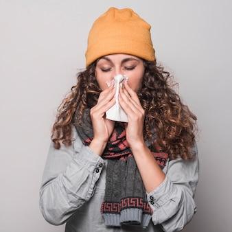 Joven mujer sonarse la nariz con un pañuelo de papel con bufanda alrededor de su cuello