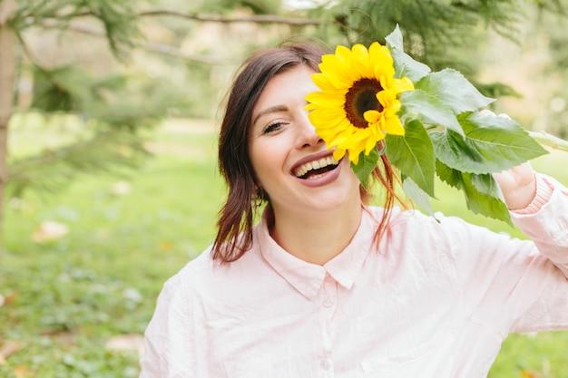 Joven mujer sonriendo y cubriendo el ojo con girasol