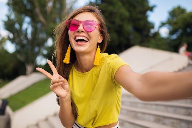 Joven mujer sonriente bastante elegante haciendo selfie en el parque de la ciudad, positiva, emocional, con top amarillo, gafas de sol rosa, tendencia de moda de estilo veraniego, cabello largo, divirtiéndose