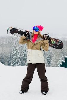 Joven mujer sonriente deportiva en invierno con snowboard, gafas