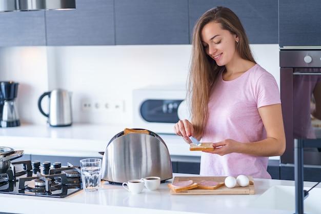 Joven mujer sonriente feliz preparando tostadas para el desayuno en la cocina en casa temprano en la mañana