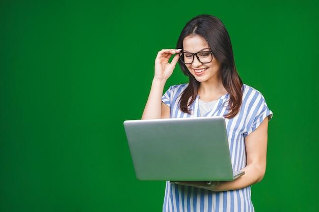 Joven mujer sonriente feliz en ropa casual con laptop y enviar correo electrónico a su mejor amiga.