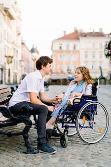 Joven mujer sonriente en la silla de ruedas y guapo en el banco mirando mutuamente en el amor, caminando en el centro de la ciudad vieja