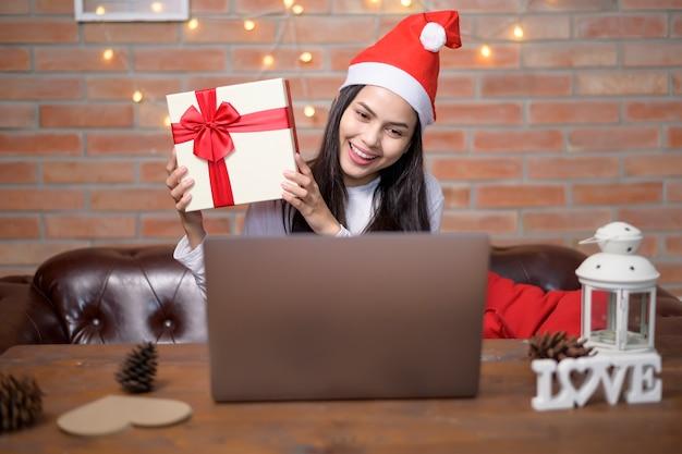 Una joven mujer sonriente con sombrero rojo de santa claus haciendo videollamadas en la red social con familiares y amigos el día de navidad.