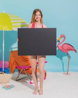 Joven mujer sosteniendo en blanco oscuro hoja de papel