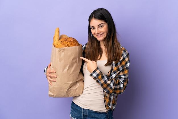 Joven mujer sosteniendo una bolsa llena de panes aislados en púrpura y señalando