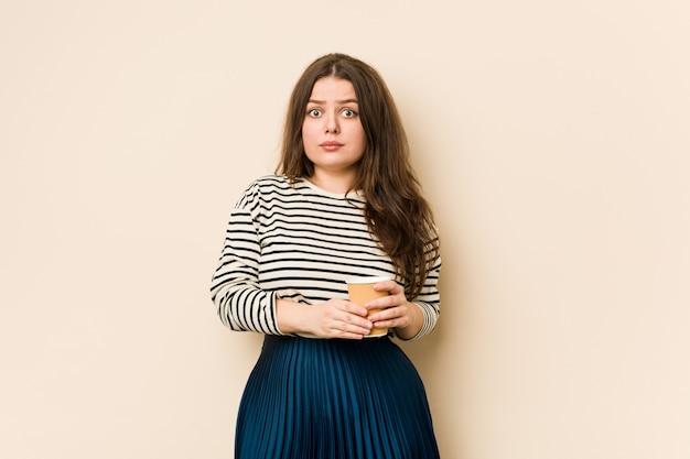 Joven mujer sosteniendo un café se encoge de hombros y abre los ojos confundidos.