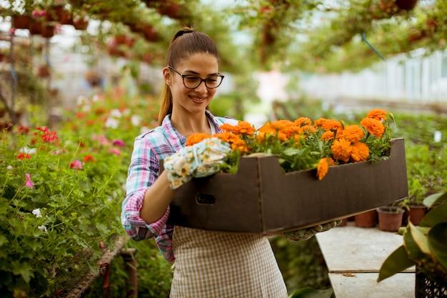 Joven mujer sosteniendo una caja llena de flores de primavera