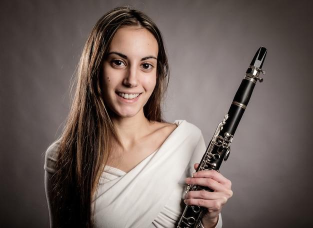Joven mujer sosteniendo un clarinete en un gris