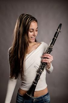 Joven mujer sosteniendo un clarinete en gris