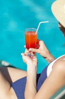 Joven mujer sosteniendo un cóctel en el banco de la piscina