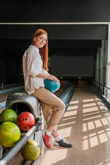 Joven mujer sosteniendo una colorida bola de boliche