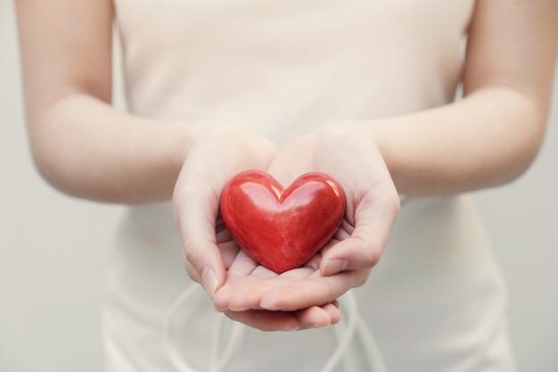 Joven mujer sosteniendo corazón rojo