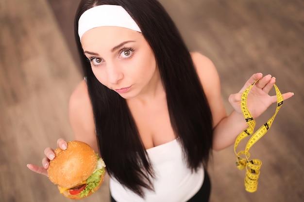 Una joven mujer sosteniendo una hamburguesa y una cinta métrica