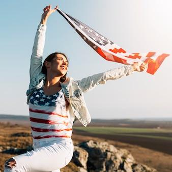Joven mujer sosteniendo ondeando la bandera de américa