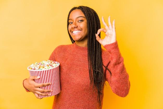 Joven mujer sosteniendo una palomitas de maíz alegre y confidente mostrando gesto bien