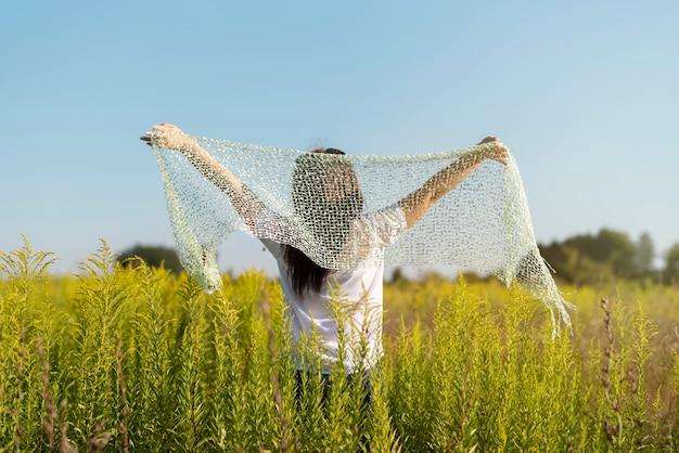 Joven mujer sosteniendo un paño en el aire