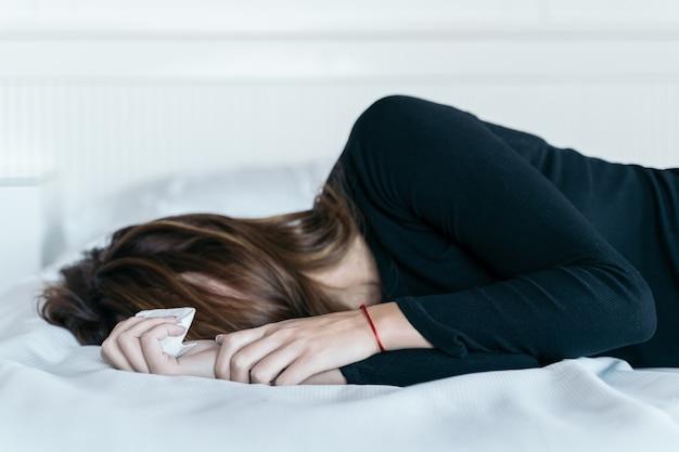 Joven mujer sosteniendo un pañuelo para secar sus lágrimas en su cama. concepto de violencia y maltrato a las mujeres.