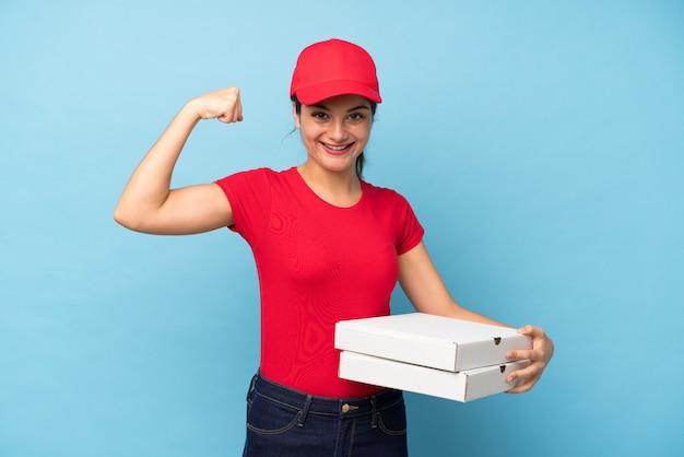 Joven mujer sosteniendo una pared de pizza celebrando una victoria