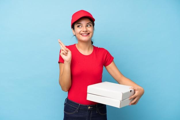 Joven mujer sosteniendo una pared de pizza con los dedos cruzando