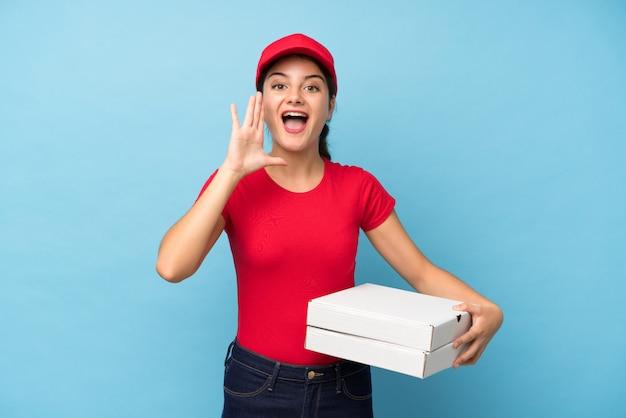 Joven mujer sosteniendo una pared de pizza gritando con la boca abierta