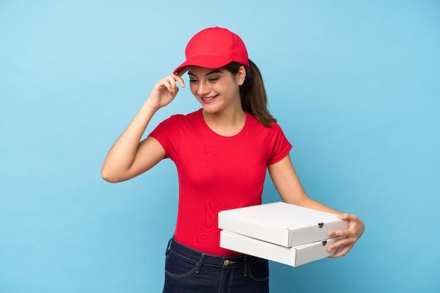 Joven mujer sosteniendo una pared de pizza riendo