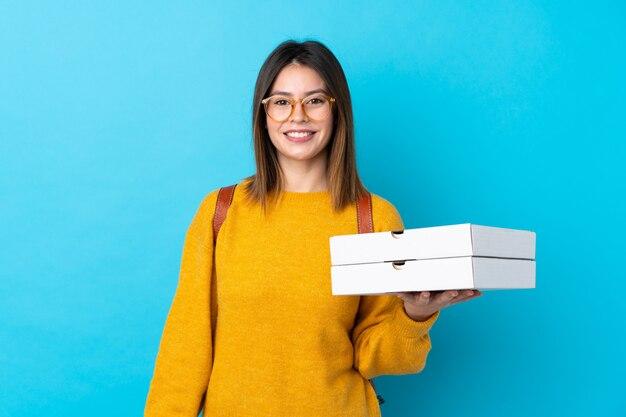 Joven mujer sosteniendo una pizza cajas sobre pared azul aislado