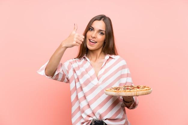 Joven mujer sosteniendo una pizza con los pulgares hacia arriba porque algo bueno ha sucedido