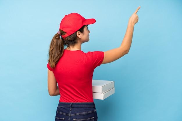 Joven mujer sosteniendo una pizza sobre pared rosa aislado apuntando hacia atrás con el dedo índice