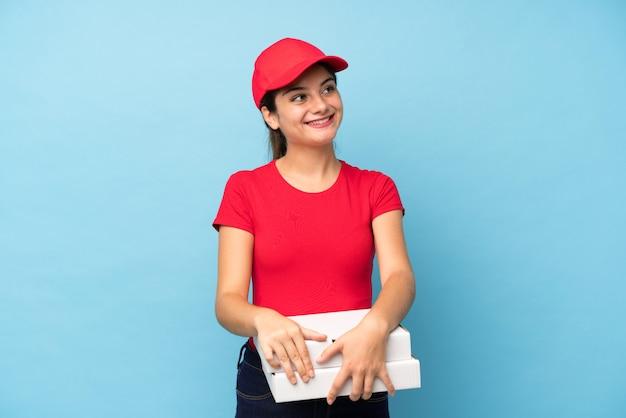 Joven mujer sosteniendo una pizza sobre pared rosa aislado riendo y mirando hacia arriba