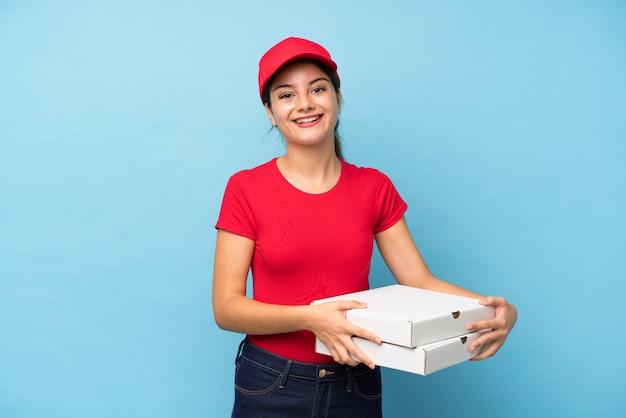 Joven mujer sosteniendo una pizza sobre pared rosa aislado riendo