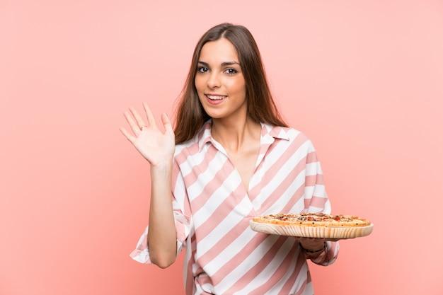 Joven mujer sosteniendo una pizza sobre pared rosa aislado saludando con la mano con expresión feliz