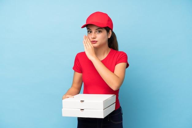 Joven mujer sosteniendo una pizza sobre pared rosa aislado susurrando algo