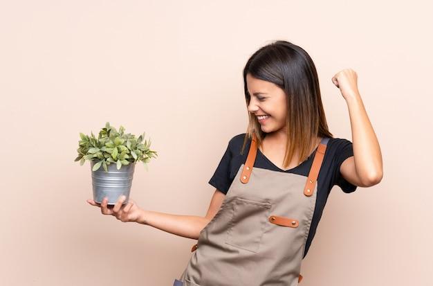 Joven mujer sosteniendo una planta celebrando una victoria
