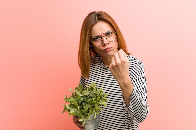 Joven mujer sosteniendo una planta mostrando el puño a la cámara, expresión facial agresiva