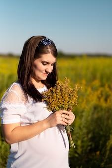 Joven mujer sosteniendo un ramo de flores en la naturaleza