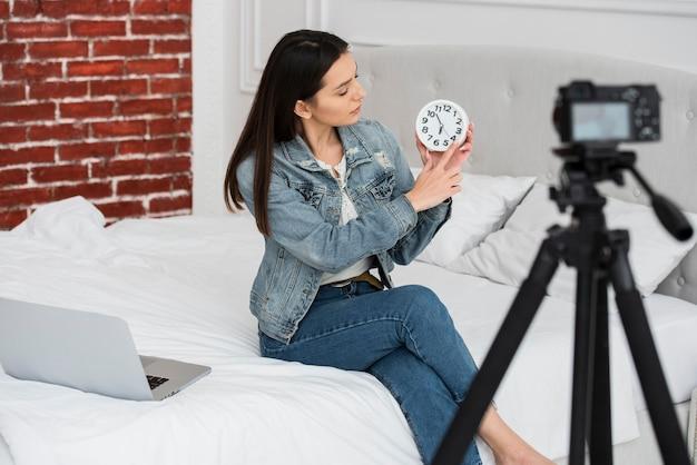 Joven mujer sosteniendo un reloj
