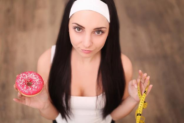 Una joven mujer sosteniendo una rosquilla y una cinta métrica