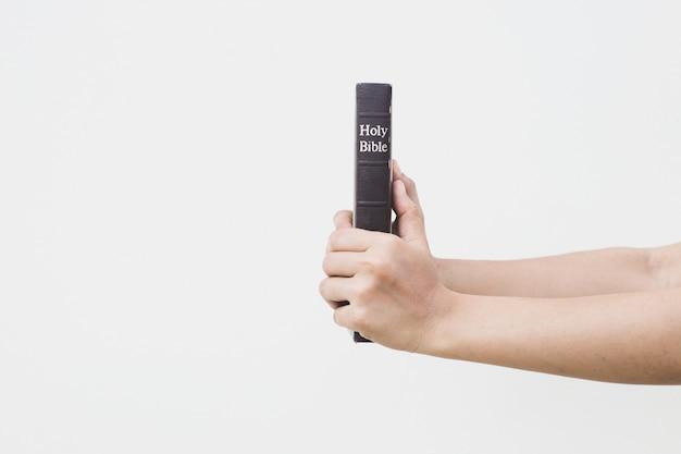 Joven mujer sosteniendo la santa biblia en sus manos
