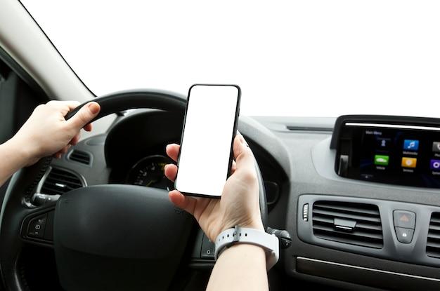 La joven mujer sosteniendo un teléfono móvil con pantalla blanca sentada en su automóvil