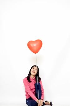 Joven mujer sosteniendo un globo rojo