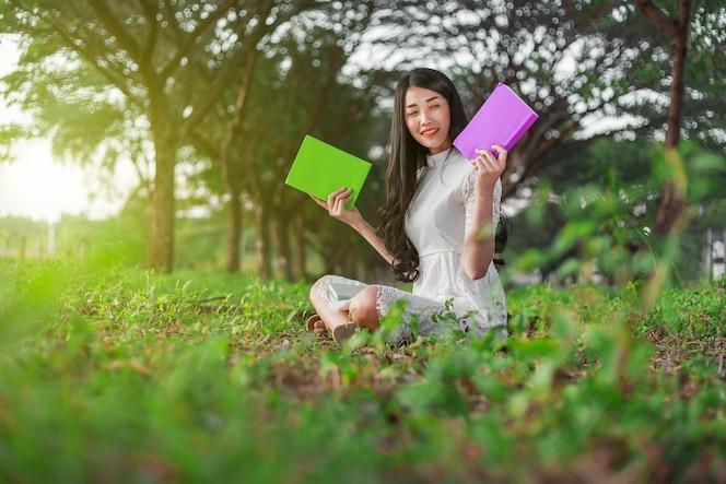 Joven mujer sosteniendo un libro en el parque