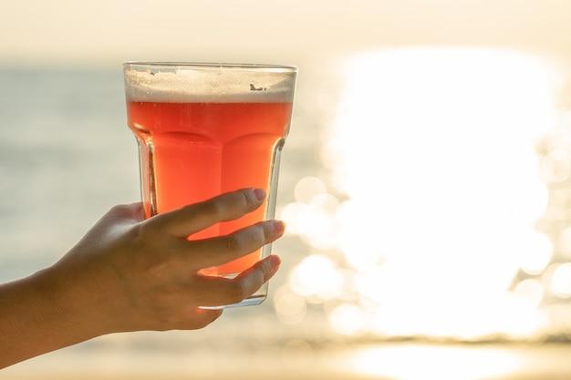 Joven mujer sosteniendo un vaso de cerveza
