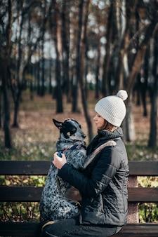 Joven mujer sostiene un perro en sus brazos