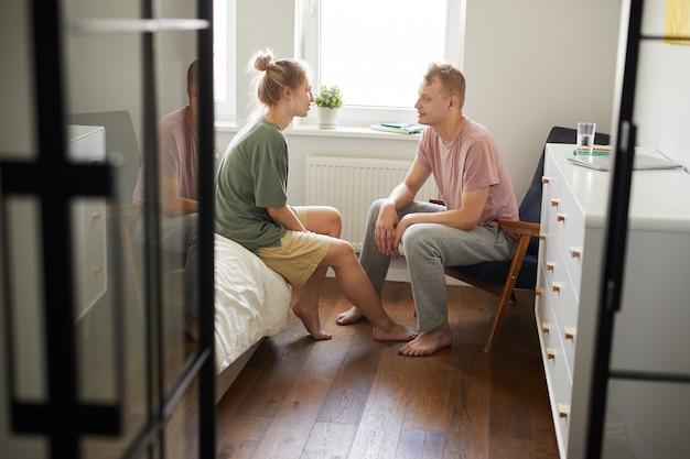 Joven mujer y su esposo interactuando en dormitorio