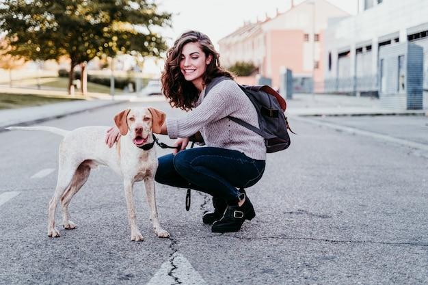 Joven mujer y su perro al aire libre caminando por la calle