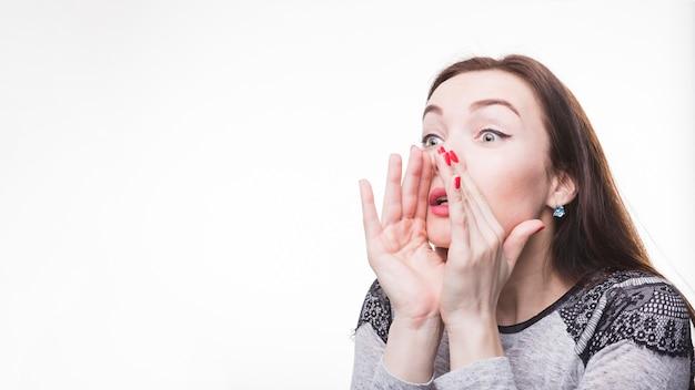 Joven mujer susurrando chismes sobre fondo blanco