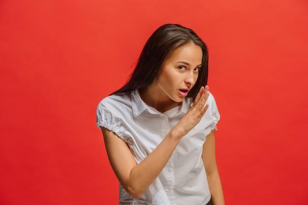 La joven mujer susurrando un secreto detrás de su mano sobre fondo rojo.